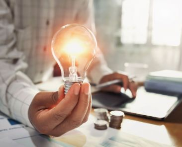 business woman hand holding lightbulb with coins stack on desk. concept saving energy power