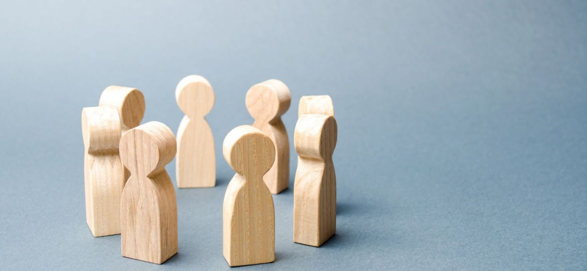 People stand in a circle on a gray background. Wooden figures of people. A circle of people. discussion, cooperation, cooperation. Communication. Business team, teamwork, team spirit. Selective focus